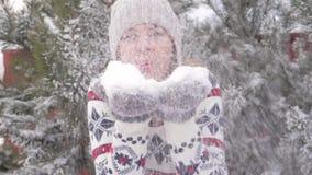 Mulher alegre bonita que tem o divertimento no movimento lento de sopro 180fps da neve do inverno filme