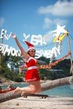 A mulher alegre bonito salta no vestido e no chapéu vermelhos de Santa na praia tropical exótica Conceito do feriado para cartões Imagens de Stock Royalty Free