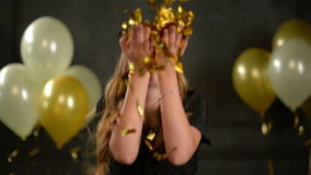A mulher alegre com cabelo e a colar longos funde em confetes sobre o fundo preto com balões de ar Retrato de bonito filme