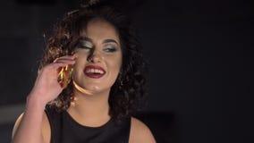 A mulher alegre com cabelo encaracolado está falando através do telefone celular no fundo preto video estoque