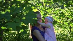 A mulher alegre com filha do bebê tem o divertimento entre ramos de árvore da tulipa 4K vídeos de arquivo
