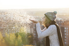 A mulher alegre com neve de sopro do chapéu do inverno lasca-se Fotos de Stock Royalty Free