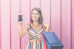Mulher alegre com os sacos de compras que mantêm o smartphone da tela vazia contra a parede cor-de-rosa foto de stock