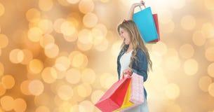 Mulher alegre com os sacos de compras sobre o bokeh imagem de stock royalty free