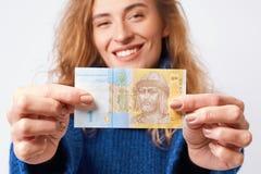A mulher alegre demonstra com o hryvnia do dinheiro que guarda o nas mãos Fotografia de Stock Royalty Free
