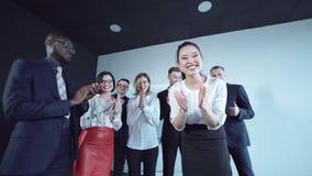 Mulher alegre do cumprimento da equipe video estoque