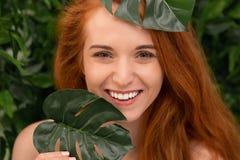 Mulher alegre do ruivo que ri através das folhas do monstera imagens de stock royalty free