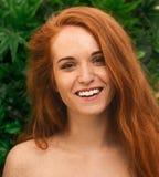 Mulher alegre do ruivo que ri através das folhas do monstera foto de stock royalty free