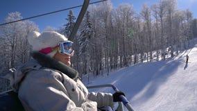 A mulher alegre do snowboarder aumenta no elevador à parte superior da montanha vídeos de arquivo