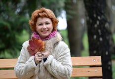 A mulher alegre dos anos médios mantém as folhas de bordo do outono disponivéis Fotografia de Stock
