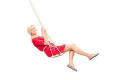 Mulher alegre em um vestido vermelho que balança em um balanço Fotografia de Stock Royalty Free