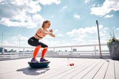 A mulher alegre está exercitando com equipamento da aptidão no terraço ensolarado imagem de stock royalty free