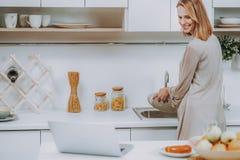 A mulher alegre está fazendo a lavagem da louça na cozinha foto de stock