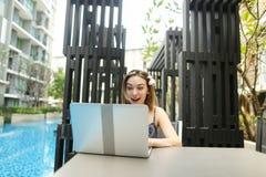 A mulher alegre exulta com o portátil perto da piscina imagens de stock