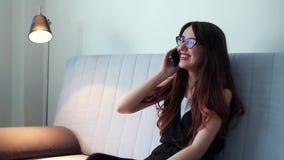 Mulher alegre feliz que fala no telefone celular e que sorri na sala de visitas em casa filme