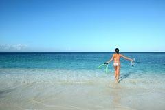 A mulher alegre no biquini funciona no mar Imagens de Stock