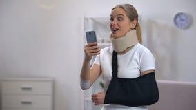 Mulher alegre no colar da espuma e no estilingue cervicais do braço que conversa na reabilitação do telefone celular video estoque