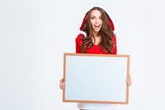 Mulher alegre no pano de Papai Noel que guarda a placa vazia Imagens de Stock Royalty Free