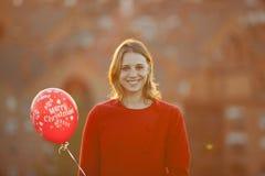Mulher alegre no revestimento vermelho que guarda um balão do Natal Fotos de Stock