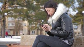 Mulher alegre no telefone em um parque da cidade que senta-se em um banco vídeos de arquivo