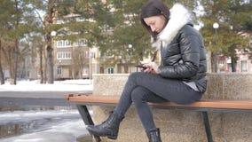 Mulher alegre no telefone em um parque da cidade que senta-se em um banco filme