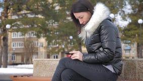 Mulher alegre no telefone em um parque da cidade que senta-se em um banco video estoque