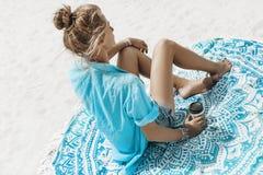 Mulher alegre nova bonita no biquini que senta-se na praia fotografia de stock royalty free