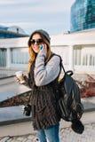 Mulher alegre nova com o caf? para ir andar no dia frio ensolarado na cidade grande A menina bonita que veste o inverno morno wol fotos de stock