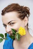 Mulher alegre nova com a rosa amarela nos dentes, th do feriado Fotos de Stock