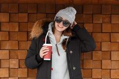 A mulher alegre nova do moderno em um chapéu feito malha cinzento nos óculos de sol em um revestimento à moda é estando e guardan imagens de stock
