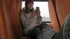 Mulher alegre nova em um chapéu vermelho, viajando pelo ônibus em um dia triste Ela que escuta a música video estoque