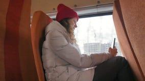 Mulher alegre nova em um chapéu vermelho, viajando pelo ônibus em um dia triste Toma imagens em um smartphone filme