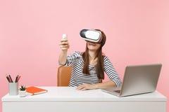 A mulher alegre nova nos auriculares da realidade virtual na cabeça que usa o controlo a distância senta o trabalho na mesa branc fotografia de stock royalty free