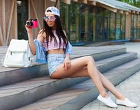 Mulher alegre nova pernudo do moderno que senta-se nas etapas na parte superior do vintage da cidade, no short das calças de brim Foto de Stock Royalty Free