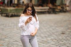 Mulher alegre nova que olha o vídeo engraçado no telefone esperto ao descansar fora fotos de stock
