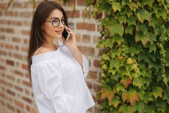 Mulher alegre nova que olha o vídeo engraçado no telefone esperto ao descansar fora imagens de stock royalty free
