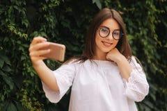 Mulher alegre nova que olha o vídeo engraçado no telefone esperto ao descansar fora foto de stock