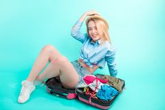 Mulher alegre nova que senta-se na bagagem com equipamento necessário fotos de stock royalty free