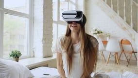 Mulher alegre nova que veste os auriculares da realidade virtual que olham um filme video de 360 VR sentar-se na cama em casa fotografia de stock royalty free