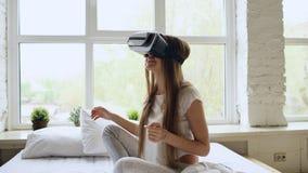 Mulher alegre nova que veste os auriculares da realidade virtual que olham um filme video de 360 VR sentar-se na cama em casa fotos de stock