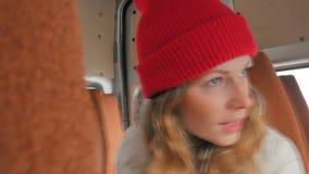Mulher alegre nova que viaja pelo ônibus em um dia triste Olha para fora a janela video estoque