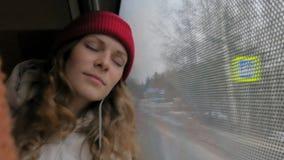 Mulher alegre nova que viaja pelo ônibus em um dia triste Olha para fora a janela vídeos de arquivo