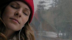 Mulher alegre nova que viaja pelo ônibus em um dia triste Olha para fora a janela filme