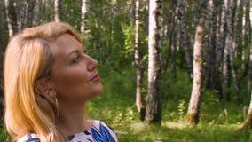 Mulher alegre que anda no bosque do vidoeiro do fundo no parque verde no dia de verão video estoque