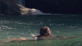 Mulher alegre que aprecia o banho na água fresca de espirrar a cachoeira na selva tropical Mulher feliz que nada dentro filme