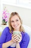 Mulher alegre que aprecia seu café foto de stock