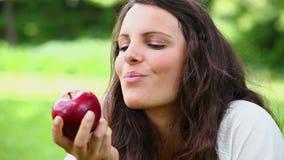 Mulher alegre que come uma maçã vermelha video estoque