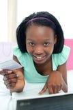 Mulher alegre que compra em linha encontrando-se em sua cama Imagens de Stock