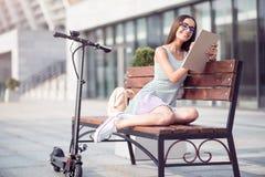 Mulher alegre que descansa no banco Imagem de Stock