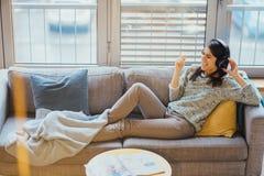 Mulher alegre que escuta a música com grandes fones de ouvido e que canta Apreciando a escuta a música no tempo livre em casa Rel fotografia de stock